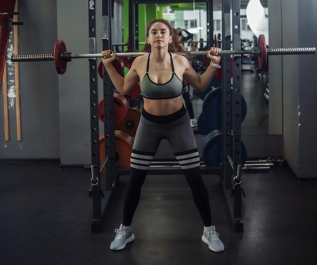 스포츠웨어에 젊은 맞는 여자는 체육관에서 그녀의 어깨에 바벨과 함께 웅크 리고 있습니다. 건강한 라이프 스타일 개념. 어려운 훈련