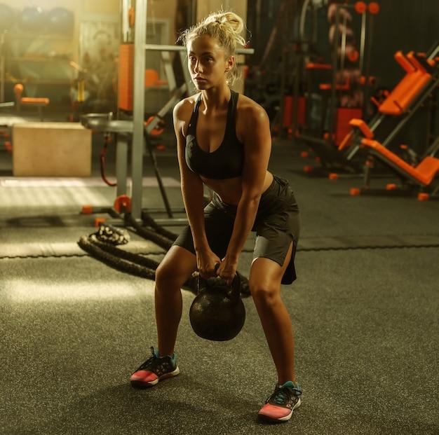 ジムでケトルベルを使って運動をしているスポーツウェアの若いフィットの女性。健康的なライフスタイルのコンセプト。フリーウェイトによるボディトレーニング。ファンクショナルトレーニング