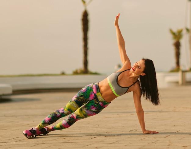 屋外でサイドプランク運動をしているスポーツウェアの若いフィット女性