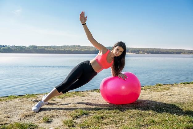 젊은 피트 니스 시간 동안 스포츠웨어에 여자와 호수에서 공 운동. 건강한 생활