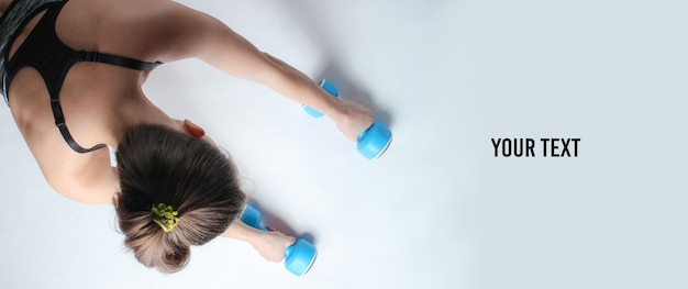 白い背景の上のダンベルで腕立て伏せをする準備をしているスポーツウェアの若いフィットの女性。スペースをコピーします。上面図