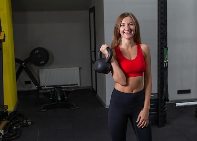 モダンなジムで重いケトルベルを保持しているスポーツウェアの若いフィット女性。フリーウェイトトレーニング