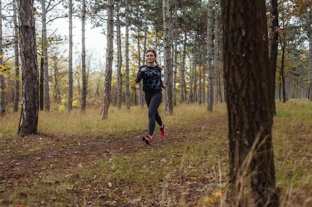 スポーツウェアの若いフィット女性は森の小道に沿って走る