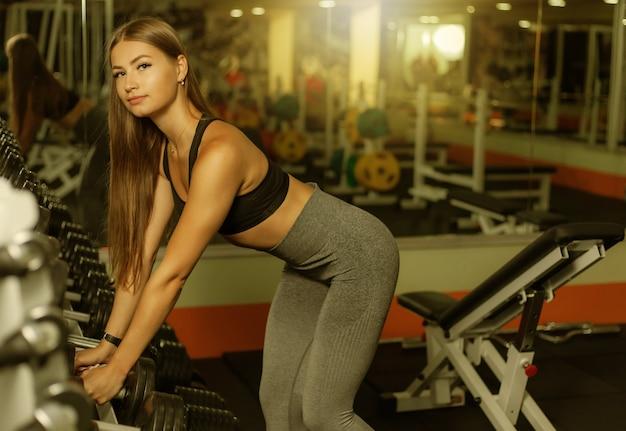 スポーツウェアの若いフィットの女性は、ジムのラックから重いダンベルを取ります。健康的なライフスタイルのコンセプト。