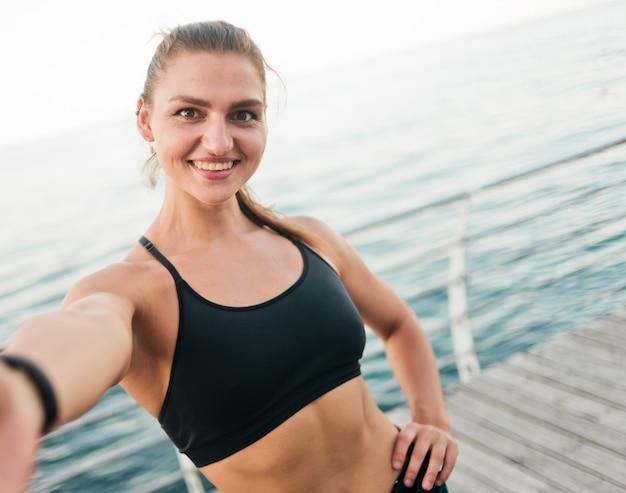 ビーチでselfieを取ってスポーツウェアの若いフィット女性