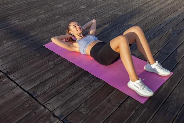 Молодая подтянутая женщина в спортивной одежде тренирует мышцы живота, лежа на коврике на рассвете на пляже