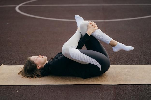 운동복에 젊은 맞는 여자 야외 놀이터에서 훈련합니다.