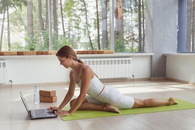 Молодая подтянутая женщина в спортивной одежде смотрит онлайн-видео с фитнес-упражнениями на ноутбуке и делает толчок