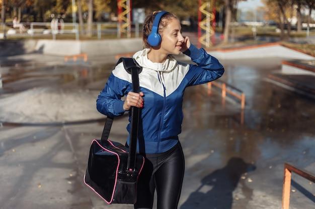 젊은 여자 가방과 스포츠 공원에서 산책하는 헤드폰 스포츠웨어에 적합합니다.