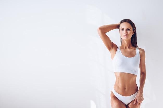 Женщина детенышей подходящая в белом женское бельё на белой изолированной стене. мускулистая стройная привлекательная самка с плоским животом. скопируйте место для текста. уход за телом, здоровая и спортивная жизнь, удаление волос, концепция йоги