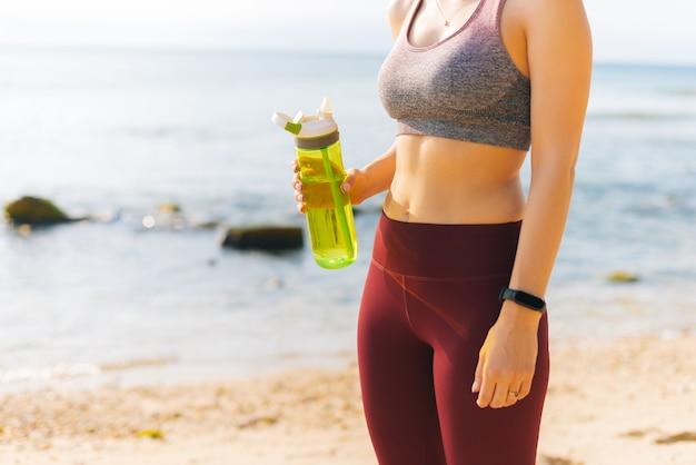 若いフィットの女性は、ビーチで水分補給しながらスポーツ運動から休憩しています。