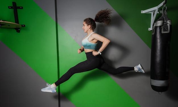 젊은 맞는 여자 스포츠 클래스에서 점프. 훈련 과정, 운동.
