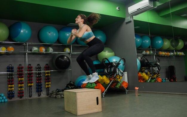 スポーツクラスで木枠にジャンプする若いフィットの女性。ファンクショナルトレーニング、トレーニングプロセス。