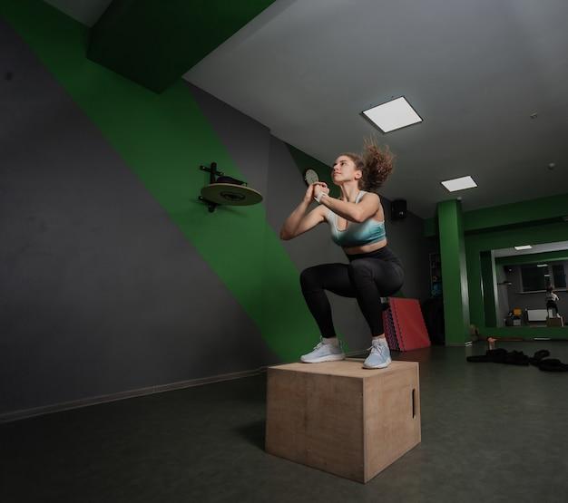 スポーツクラスで木枠にジャンプする若いフィットの女性。ファンクショナルトレーニング、トレーニング。