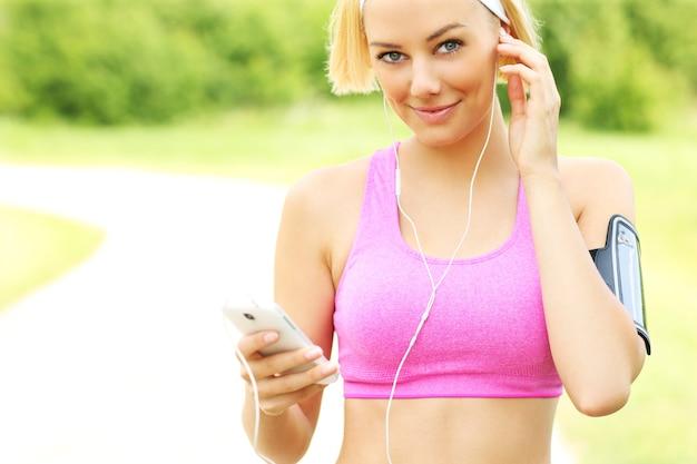 Молодая женщина подходит, слушая, размышляя во время бега в парке