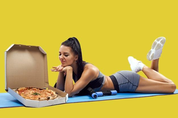 フィットネスマットの上に横たわって、ピザの箱を見ながら嫌悪感を表現している若いフィットの女性。健康体のジャンクフードの敵。体重を減らし、太った概念を得る