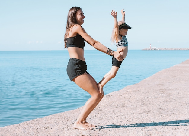 Young fit woman mom with little cute girl exercising on beach together