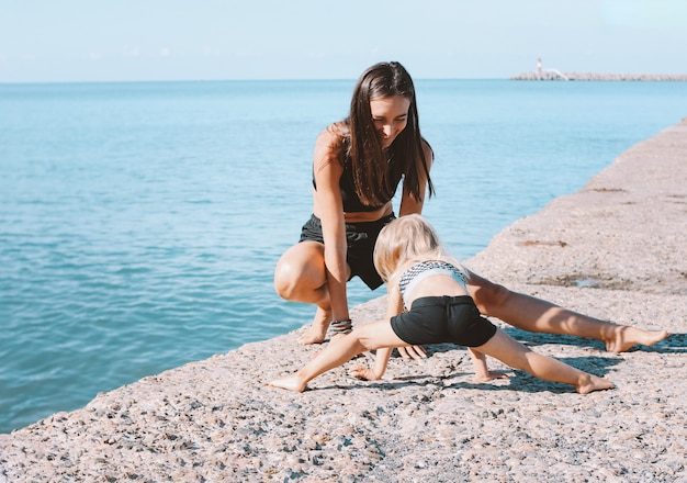 Young fit woman mom with little cute girl exercising on morning beach together