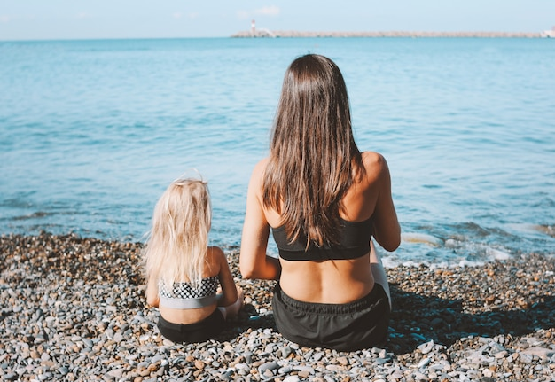 Young fit woman mom with little cute girl sitting on beach together
