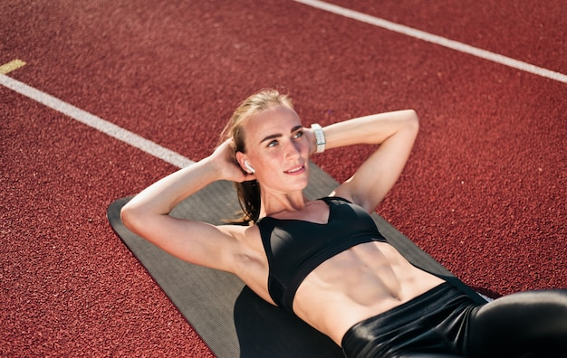 Young fit woman perfoms her body doing twisting exercise for abdominal muscles on mat at stadium track with red coating
