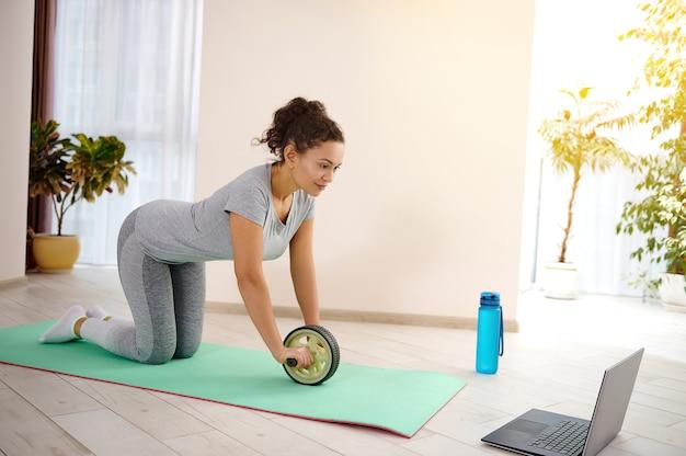 체조 롤러를 사용하여 노트북을 통해 복근 운동을 수행하는 젊은 맞는 여자. 홈 개념에서 피트니스