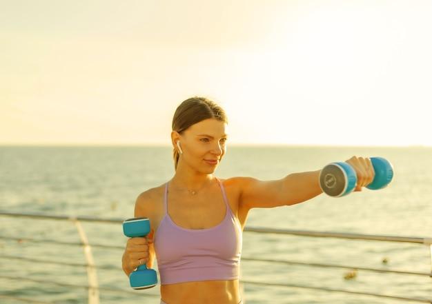젊은 여성은 일출 때 해변에서 아령으로 펀치를 연습합니다. 프리 웨이트를 이용한 아침 운동