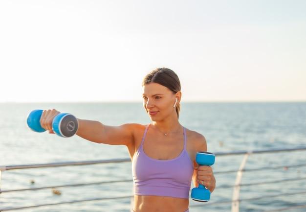 젊은 맞는 여자 관행 일출 해변에서 아령으로 펀치. 무료 웨이트를 사용한 아침 운동