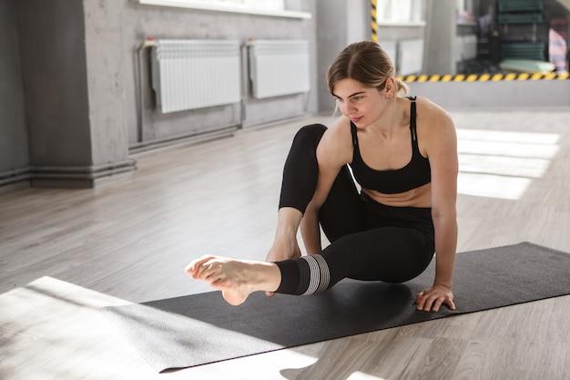 ヨガスタジオでバランスと強さのアサナを練習する若い女性にフィット