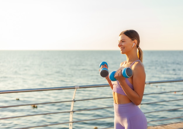 Young fit woman practicing exercise with dumbbells on the beach at sunrise. morning workout with free weights