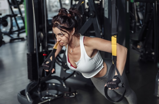 ジムでフィットネスロープで腕立て伏せを練習している若いフィットの女性