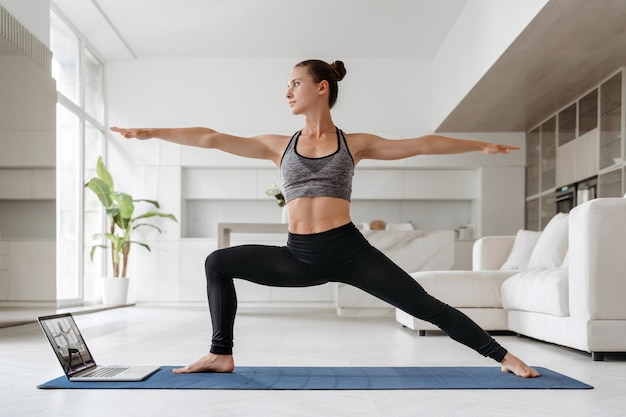 Young fit woman practicing yoga at home using laptop computer