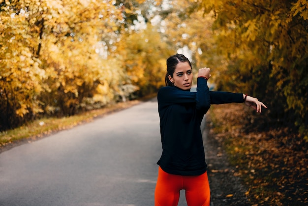 Young fit woman preparing for autumn training in park.