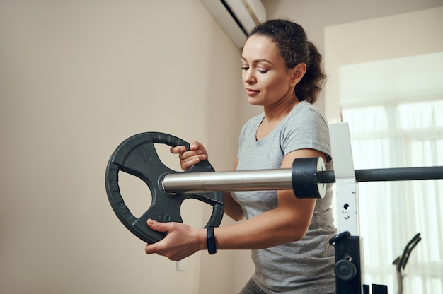 A young fit woman putting a metal disc on a barbell during heavy bodybuilding workout. exercising at home.