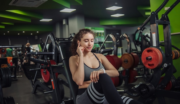 Young fit woman sitting on a bench in the gym. looks at the watcha and touches the earphones. modern gadgets. rest between exercises.