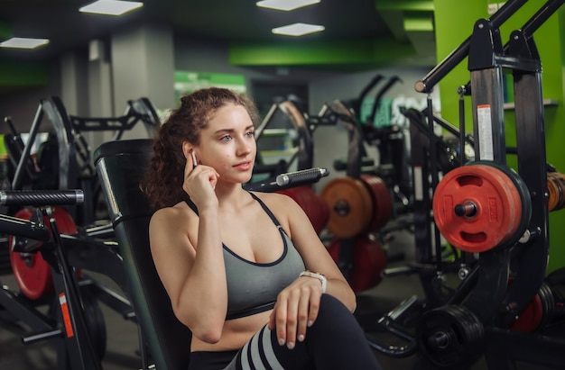 Young fit woman sitting on a bench in the gym and touches earphones. modern gadgets. rest between exercises.