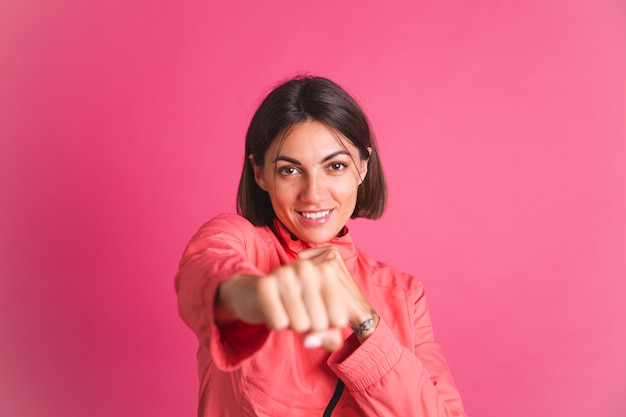 Young fit woman in sport wear jacket on pink does fight box gesture