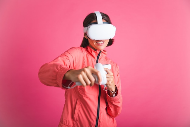 Young fit woman in sport wear jacket and virtual reality glasses playing boxing fight games on pink