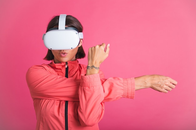 Young fit woman in sport wear jacket and virtual reality glasses stretching herself on pink