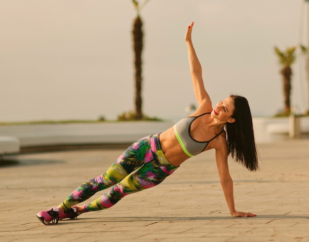 Young fit woman in sportswear doing side plank exercise outdoors