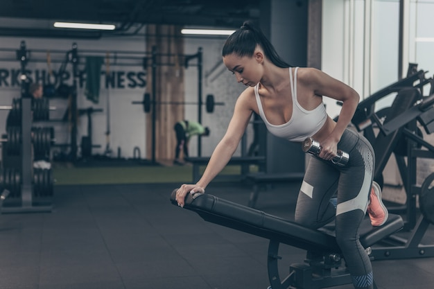 Young fit woman in sportswear exercising with dumbbells at the gym, copy space.