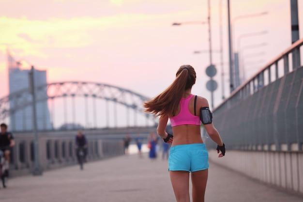 Giovane donna adatta in abiti sportivi all'aperto