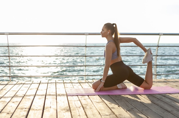 Young fit woman in sportswear practices yoga asana exercise pose on mat at sunrise on the beach