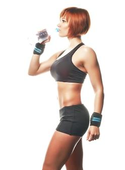 Молодая подходят женщина стоя и носить ремни и питьевой воды с бутылкой. изолированный, белый фон, студия выстрел.