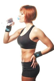 立ってストラップを着用し、ボトルで水を飲む若いフィットの女性。孤立した、白い背景、スタジオショット。