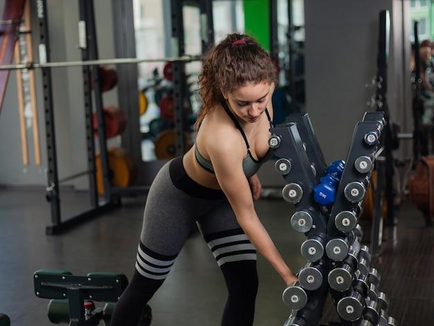 젊은 맞는 여자는 체육관에있는 선반에서 아령을 걸립니다. 무료 웨이트 트레이닝