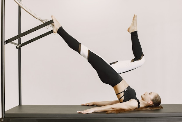 ジムでトレーニングする若いフィットの女性。黒のスポーツウェアを着ている女性。装備でストレッチ白人の女の子。