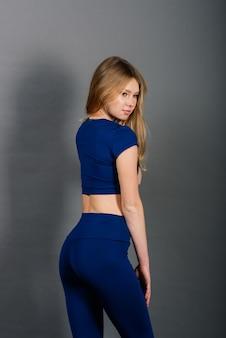 スポーツ衣装、スタジオ写真でトレーニングする若いフィットの女性