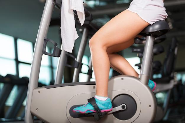 체육관에서 운동용 자전거로 훈련하는 젊은 여성