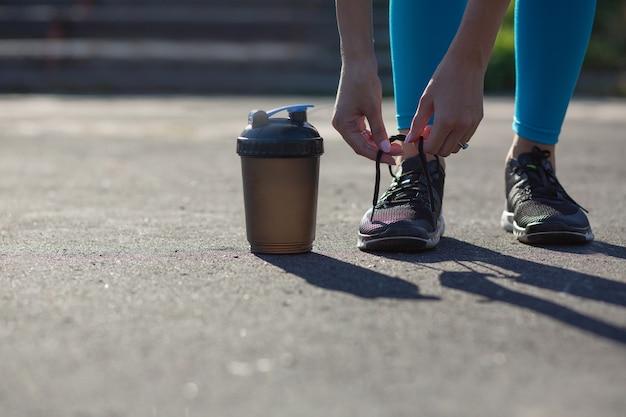 Молодая здоровая женщина, завязывающая шнурки на стадионе во время бега трусцой. место для текста