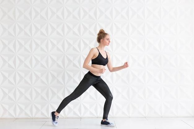 Young fit woman wearing sportswear posing near white wall